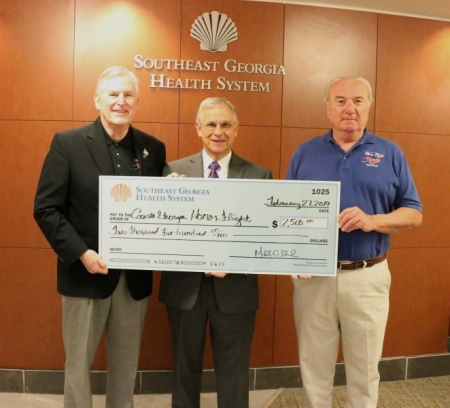 Michael D. Scherneck, president & CEO, Southeast Georgia Health System (center) presents $2,500 donation to Coastal Georgia Honor Flight board members Dave Olender, president, (left) and Mark Beaudry, vice president and co-flight leader (right)
